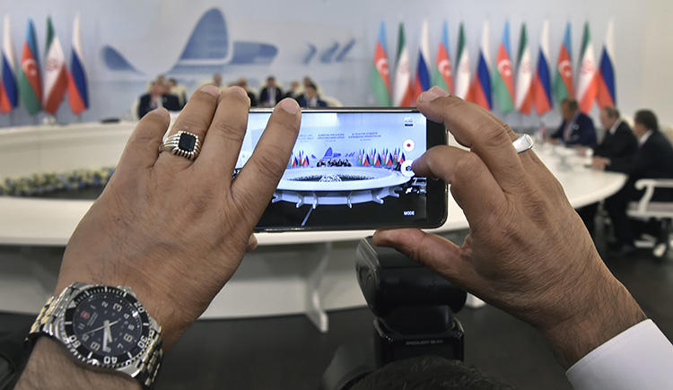 A cell phone takes photos of an August 2016 meeting in Baku between the presidents of Russia, Iran, and Azerbaijan. President Ilham Aliyev claims internet is 'free of censorship' in Azerbaijan, but authorities have blocked access to critical news websites. (Alexander Nemenov/Pool/AP)