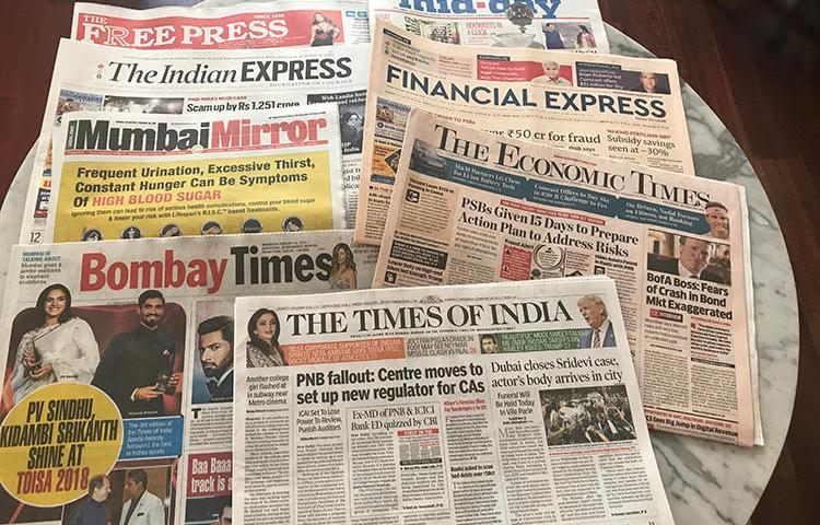 Copies of Indian newspapers are spread across a desk during a CPJ visit to the country in early 2018. (CPJ/Aliya Iftikhar)