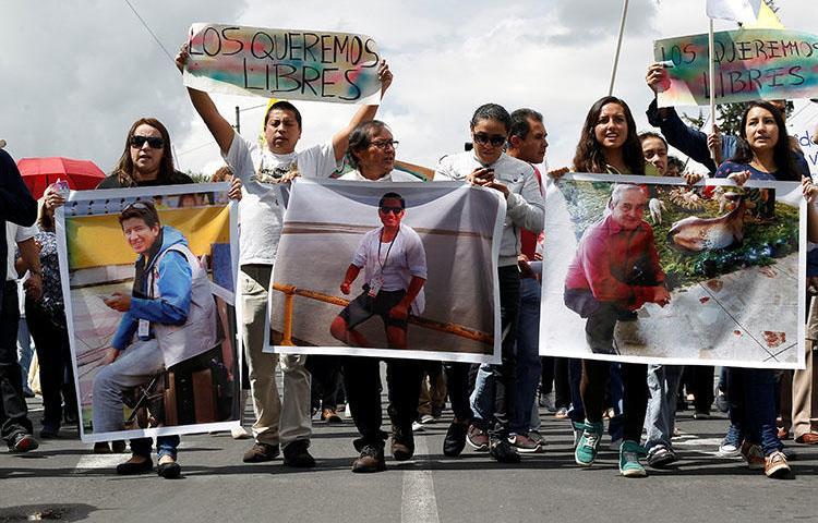 Familiares y amigos en Quito muestran fotos el 1 de abril del reportero gráfico ecuatoriano Paúl Rivas, a la izquierda, el periodista Javier Ortega, centro, y su chófer Efraín Segarra, quienes fueron secuestrados cerca de la frontera con Colombia y luego asesinados. (Reuters / Daniel Tapia)
