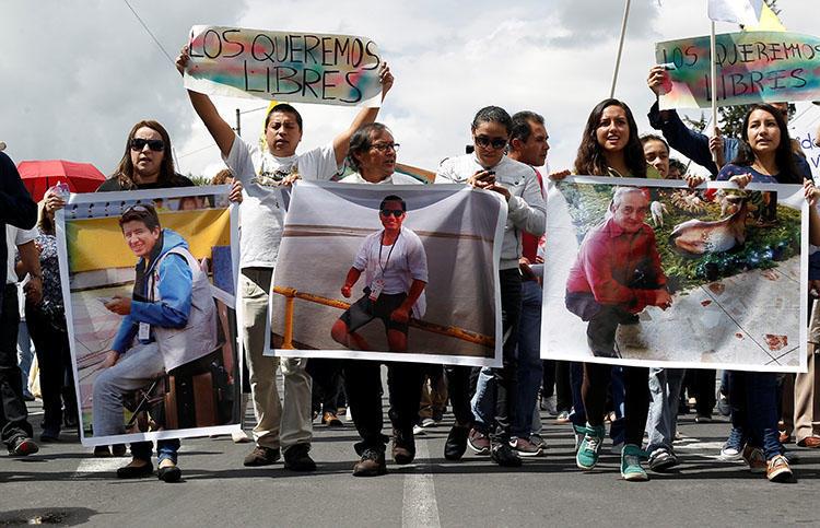 Caption: Parentes e amigos seguram fotos em Quito em 1º de abril, do fotojornalista equatoriano Paul Rivas, à esquerda, do jornalista Javier Ortega, do centro, e de seu motorista Efrain Segarra, que foram sequestrados perto da fronteira colombiana e depois mortos. (Reuters / Daniel Tapia)