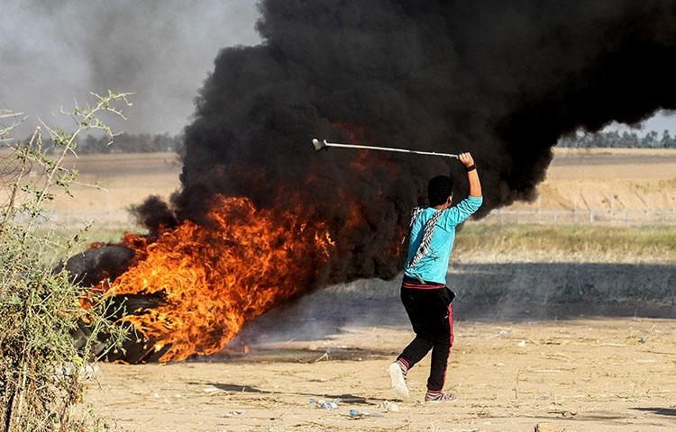 A Palestinian youth swings a sling shot during clashes after a demonstration near the border with Israel, east of Khan Younis in the Gaza Strip on April 1, 2018. (AFP/Said Khatib)