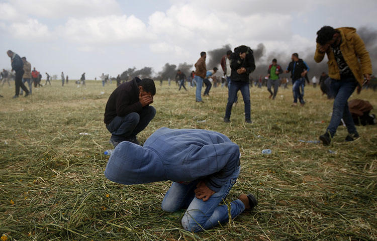 Palestinian protesters cover from teargas fired by Israeli soldiers during clashes with Israeli troops along the Gaza Strip border with Israel, east of Khan Younis, Gaza Strip, on March 30, 2018. (AP/Adel Hana)