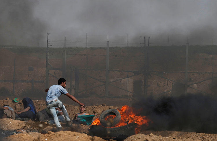 Palestinian demonstrators take cover during clashes with Israeli troops on the Israel-Gaza border, east of Gaza City, April 13, 2018. (Reuters/Mohammed Salem)