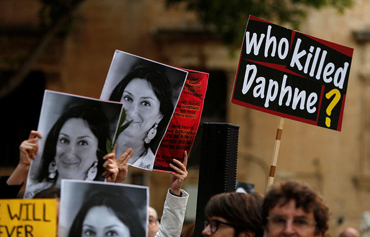People hold up photos of anti-corruption journalist Daphne Caruana Galizia during a vigil on April 16, 2018, marking the sixth month anniversary of her assassination in Malta. The Council of Europe appointed Pieter Omtzigt as a special rapporteur to monitor the ongoing investigation into her murder, according to reports. (Reuters/Darrin Zammit Lupi)