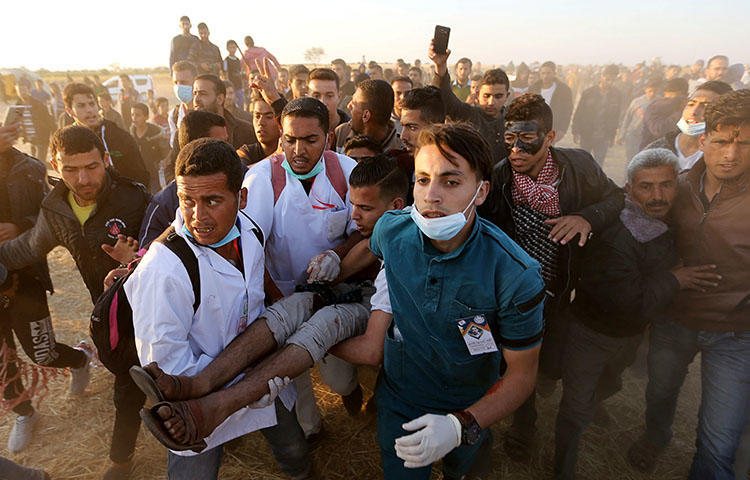 A wounded Palestinian demonstrator is evacuated during clashes with Israeli troops at the Israel-Gaza border at a protest demanding the right to return to their homeland, in the southern Gaza Strip on April 9, 2018. Photojournalist Yaser Murtaja was injured when a live round hit him in the abdomen while he was covering protests in the area east of Khan Younis city and died the next day from injuries, according to reports. (Reuters/Ibraheem Abu Mustafa)