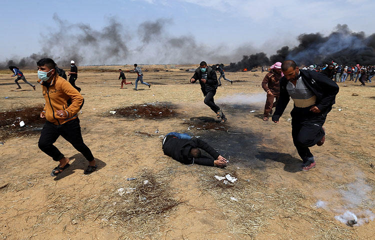 A wounded Palestinian falls to the ground during clashes with Israeli troops at a protest in the southern Gaza Strip on April 27, 2018. At least seven journalists were injured on April 27 while covering the protests, according to CPJ research. (Reuters/Ibraheem Abu Mustafa)