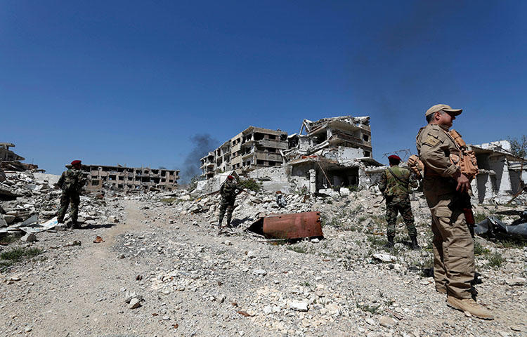 Members Syrian President Bashar Assad's forces stand guard near destroyed buildings in eastern Ghouta on April 2, 2018. Two members of a Turkish-funded militant group on March 21, 2018, attacked a Syrian cameraperson as he was covering the arrival of refugee convoys from eastern Ghouta, according to reports. (Reuters/Omar Sanadiki)