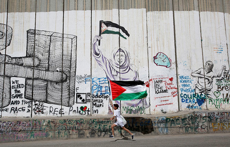 A participant runs past the Israeli barrier in the occupied West Bank during the annual Palestine Marathon in Bethlehem on March 23, 2018. Palestinian Preventive Security Forces on April 18 arrested Hazem Naser at home in the northern West Bank city of Tulkarem, according to news reports. (Reuters/Mussa Qawasma)