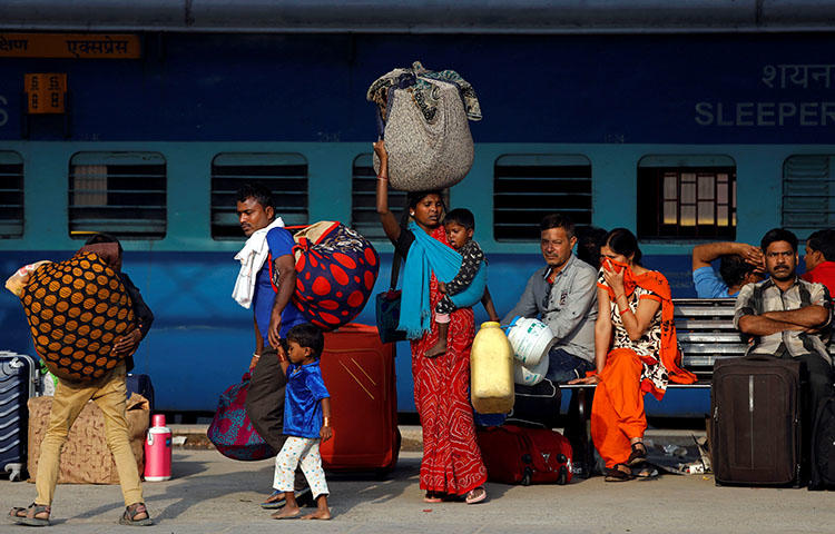 Passengers walk along a platform carrying luggage at a railway station in New Delhi, India in April 2018. Two unidentified persons on April 17 threw a gasoline bomb at the house of Patricia Mukhim, editor of the local Shillong Times newspaper, according to reports. (Reuters/Saumya Khandelwal)