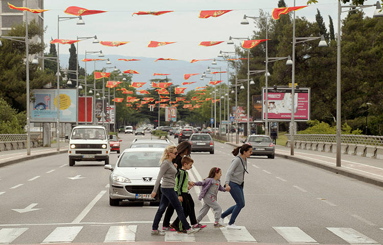 People cross the street decorated with flags in May 2016 as part of the celebrations for Montenegro's Independence Day. A car bomb exploded outside a journalist's home in Montenegro's northern town of Bijelo Polje on April 1, 2018, according to news reports. (Reuters/Stevo Vasiljevic)