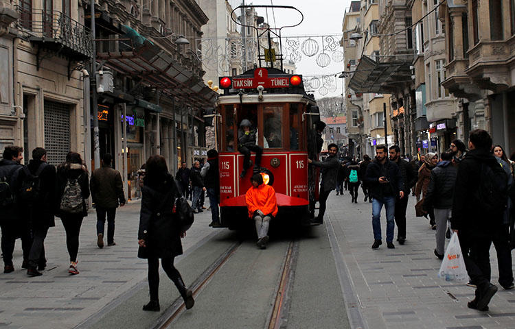 Boys stand on the edges of a vintage tram as it runs along the main shopping and pedestrian street of Istiklal in central Istanbul, Turkey in January 2018. Turkey continues to crackdown on media. (Reuters/Murad Sezer)