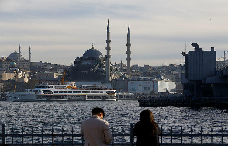 """People relax near Golden Horn in Istanbul, Turkey on April 4, 2018. An Istanbul court convicted in a retrial Hasan Cemal, a veteran journalist and a columnist for the news website T24, on charges of """"making propaganda for a [terrorist] organization,"""" according to news reports. (Reuters/Osman Orsal)"""