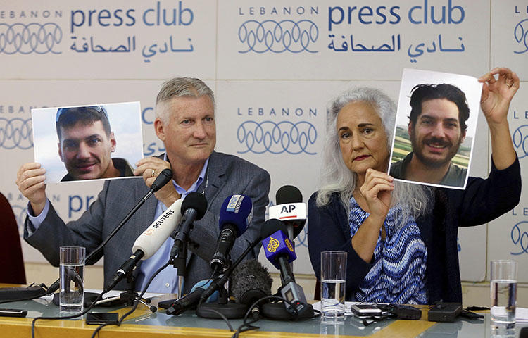 Marc and Debra Tice, the parents of Austin Tice, who went missing in Syria in 2012, hold up photos of him during a press conference at the Press Club in Beirut, Lebanon, on July 20, 2017. (AP/Bilal Hussein)
