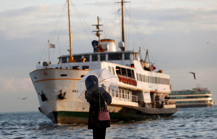 A woman takes pictures with her cellphone as a ferry approaches Besiktas pier in Istanbul, Turkey on March 27, 2018. Turkish authorities continue to crackdown on the country's press. (Reuters/Murad Sezer)