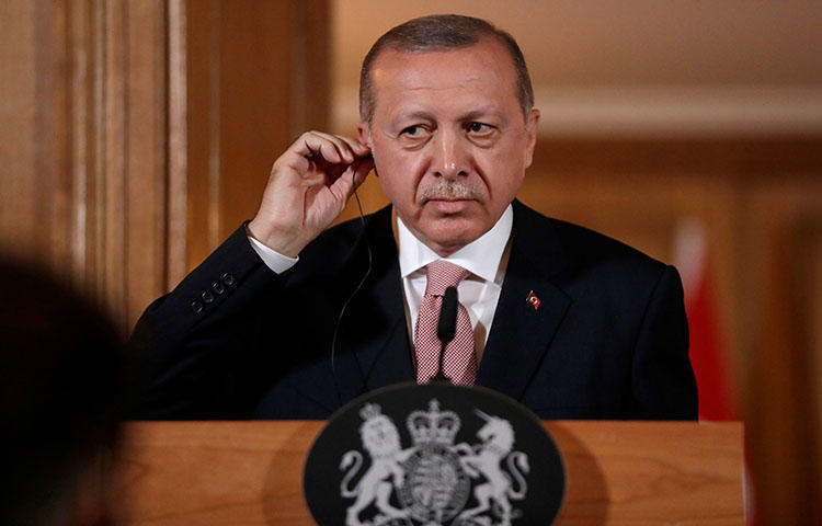 Turkey's President Recep Tayyip Erdogan listens via an interpreter as Britain's Prime Minister Theresa May speaks during a joint press conference in London on May 15, 2018. During the press conference Erdogan said that Turkey's jailed journalists are not, in fact, journalists, according to reports. (AFP/Matt Dunham)