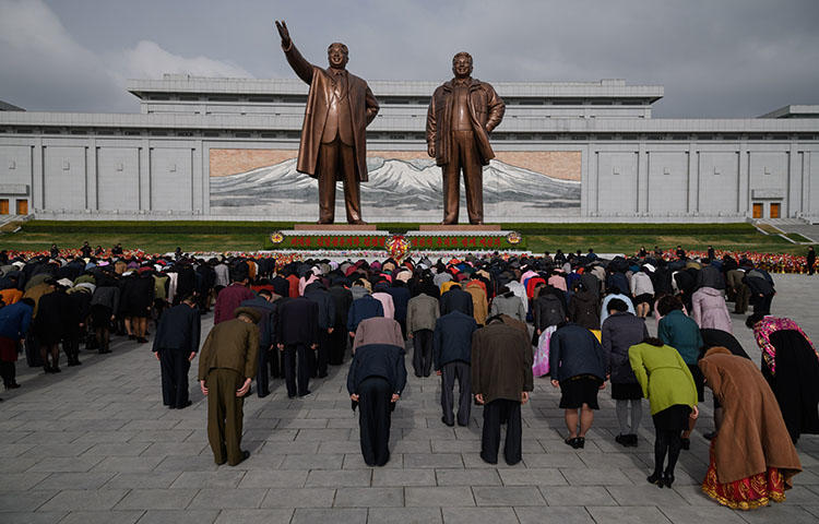 People bow as they pay their respects before the statues of late North Korean leaders Kim Il Sung and Kim Jong Il at Mansu Hill in Pyongyang on April 15, 2018. Eight South Korean journalists were denied entry visas into North Korea to cover the dismantling of a nuclear test site in North Korea, according to news reports. (AFP/Ed Jones)