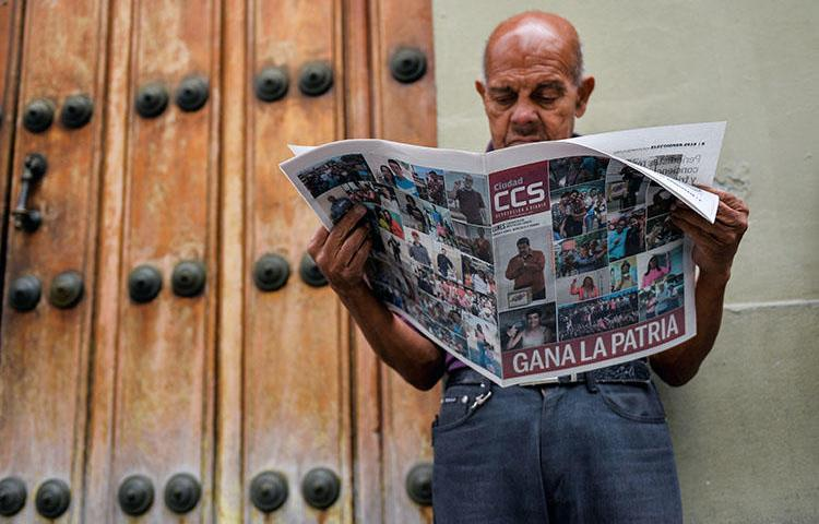 Em Caracas, um homem lê um jornal que alude à vitória do presidente reeleito Nicolas Maduro na eleição presidencial venezuelana de 21 de maio de 2018. O órgão regulador nacional de telecomunicações da Venezuela abriu uma investigação, em 22 de maio, sobre o conteúdo publicado no site do El Nacional, o maior jornal diário independente do país. (Luis Robayo/AFP)