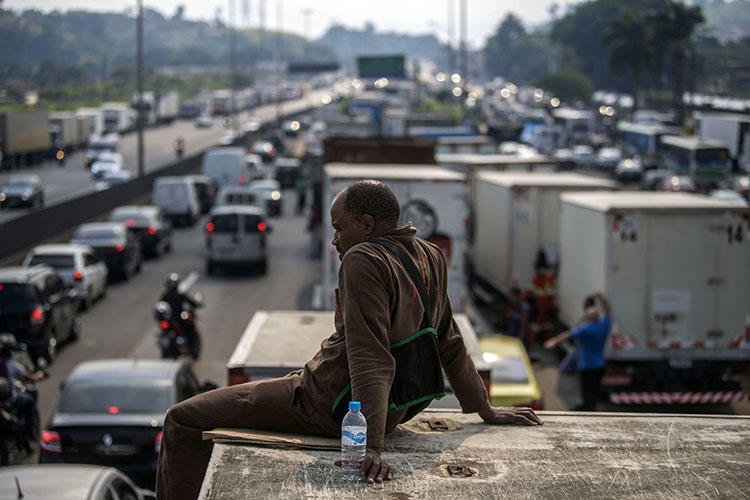 Brazilian truck drivers partially block a road during a nationwide strike to protest rising fuel costs in Rio de Janeiro, Brazil, on May 25, 2018. A radio host in northeastern Brazil has been subject to a series of threats in the first four months of 2018. (Mauro Pimentel/AFP)