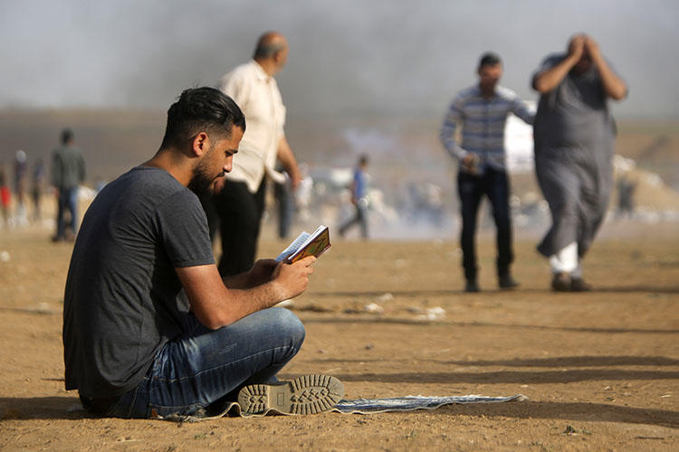 A Palestinian man reads a book during clashes with Israeli forces along the border with the Gaza strip east of Jabalia on May 18, 2018. An Israeli police officer assaulted a Palestinian journalist covering pro-Gaza protests in Haifa on May 18. (Mohammed Abed/AFP)