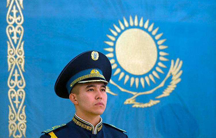 A Kazakh soldier stands in front of the national flag at the presidential palace in Astana, in 2014. CPJ is joining calls for the country to revise its repressive press laws. (AFP/Alain Jocard)