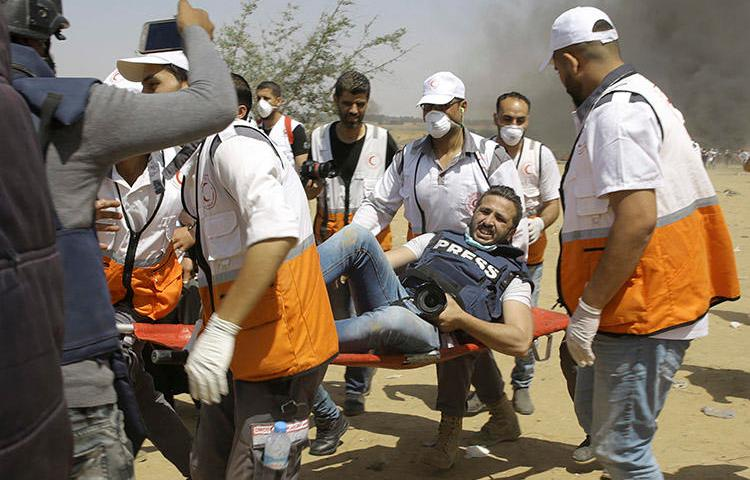Palestinian medics evacuate a wounded photographer during a protest at the Gaza Strip's border with Israel on May 11, 2018. (AP/Adel Hana)