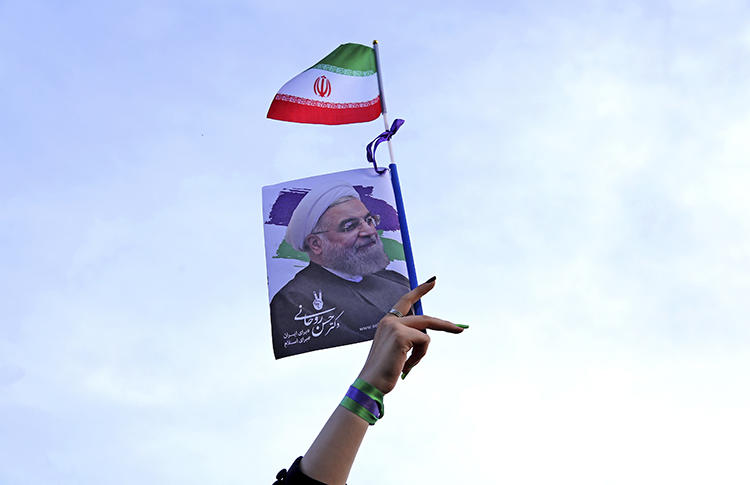 A supporter of Iranian President Hassan Rouhani waves a poster with his image at an election rally in Tehran in May 2017. Rouhani's campaign promises include calls for greater press freedom and access to information. (AP/Ebrahim Noroozi)