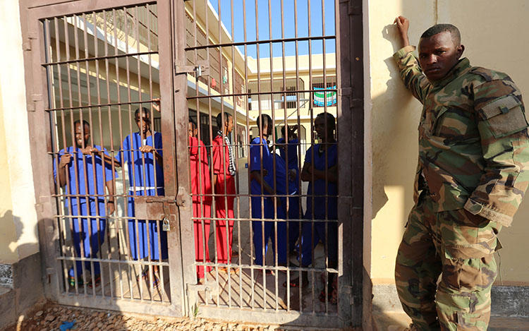 A soldier stands outside Garowe prison as prisoners stand behind the locked gate in Garowe, Puntland, in northeastern Somalia, on December 14, 2016. Puntland authorities detained a journalist without charge on May 4, 2018. (Reuters/Feisal Omar)
