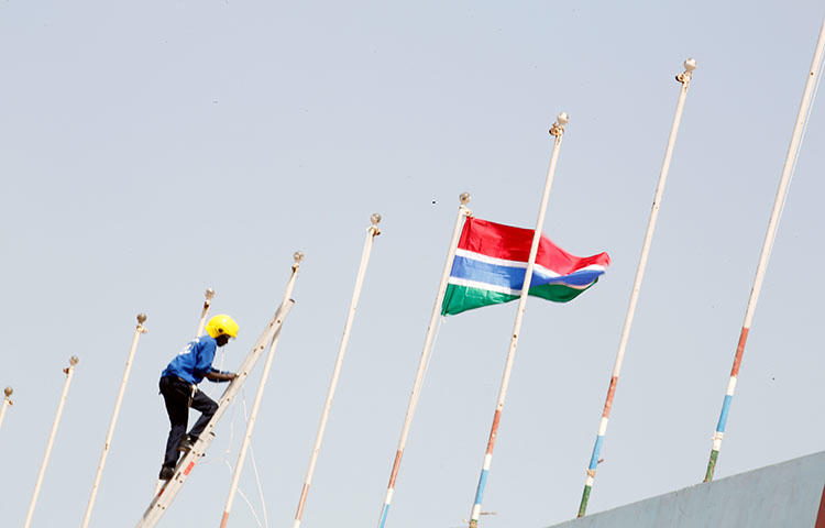 A man fixes Gambia's flag on Feburary 16, 2017, during preparations for the swearing-in ceremony for Gambia's new president, Adama Barrow. Gambia's Supreme Court decided on May 9, 2018, to declare criminal defamation unconstitutional, but upheld segments of the country's criminal code on sedition and false news, according to reports. (Reuters/Thierry Gouegnon)