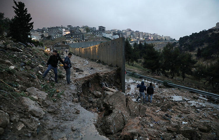 Palestinians stand next to a collapsed part of the Israeli barrier near a refugee camp in East Jerusalem on April 26, 2018. Israeli internal security forces and police on April 18 posted a Defense Ministry order to the door of Elia Youth Media Foundation ordering its closure, according to media reports. (Reuters/Ammar Awad)