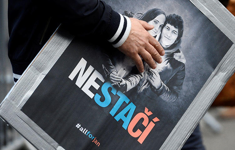 A poster with the images of Slovak journalist Jan Kuciak and his fiancee Martina Kusnirova who were found shot to death in their home on February 25, 2018. Slovak police in Bratislava on May 16, 2018, seized the mobile phone of Czech investigative reporter Pavla Holcova while questioning her for their investigation into the couple's murder, according to reports. (Reuters/Radovan Stoklasa)