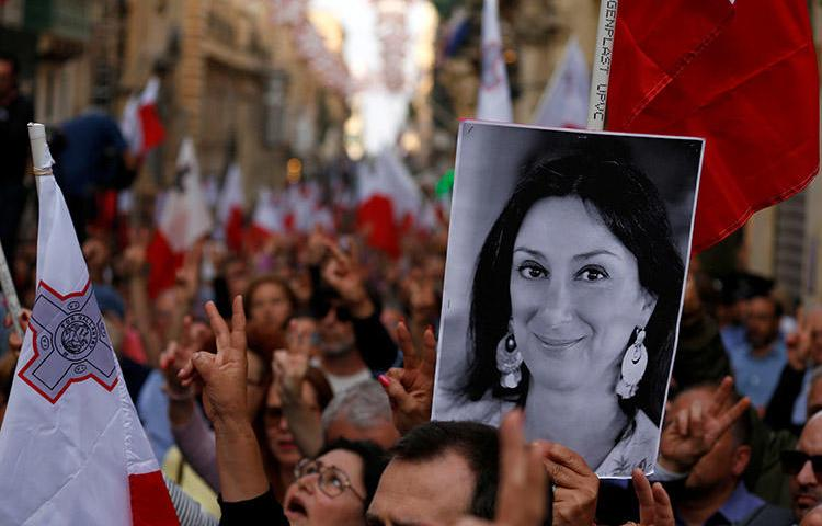 A poster of murdered journalist Daphne Caruana Galizia is carried at a protest against government corruption revealed by the Daphne Project, in Valletta, Malta, on April 29. Reporting on corruption can be a dangerous assignment. (Reuters/Darrin Zammit Lupi)
