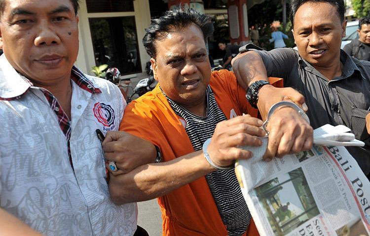 Indian crime boss Rajendra Sadashiv Nikhalje, center, is escorted by Indonesian police in 2015 after his arrest in Bali. A Mumbai court today sentenced him to life in prison for the murder of journalist Jyotirmoy Dey. (Reuters/Nyoman Budhiana/Antara Foto)