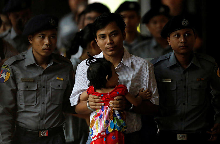 Handcuffed Reuters journalist Kyaw Soe Oo carries his daughter while arriving for a court hearing in Yangon, Myanmar on May 2. Kyaw Soe Oo and his colleague Wa Lone were reporting on a massacre in Rakhine state at the time of their arrest in December. (Reuters/Ann Wang)