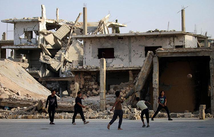 Children play football in front of a damaged building in a rebel-held neighborhood of Daraa in southern Syria on May 7, 2018. Unknown gunmen killed journalist Ibrahim al-Munjar in Daraa on May 17. (Mohamad Abazeed/AFP)