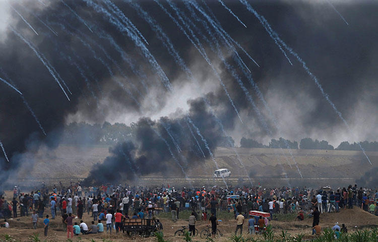 Tear gas canisters are fired by Israeli forces at Palestinian demonstrators on May 4, 2018. At least five Palestinian journalists were injured covering protests in the Gaza Strip on May 4 as the Israel Defense Forces used tear gas and fired live rounds to disperse demonstrators, according to reports. (Reuters/Mohammed Salem)