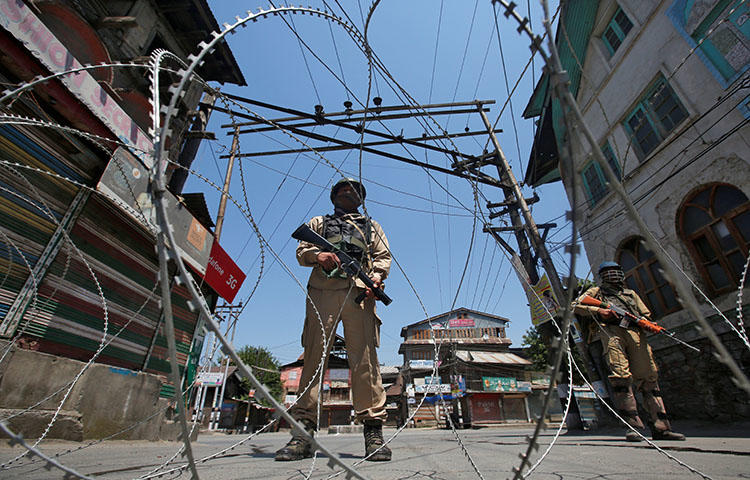 Indian policemen stand guard behind concertina wire during a strike in the town of Srinagar in the state of Jammu and Kashmir on May 21, 2018. A Kashmiri freelance photographer, Masrat Zahra, told CPJ that she has faced online harassment and threats after a photograph of her, captioned with the word