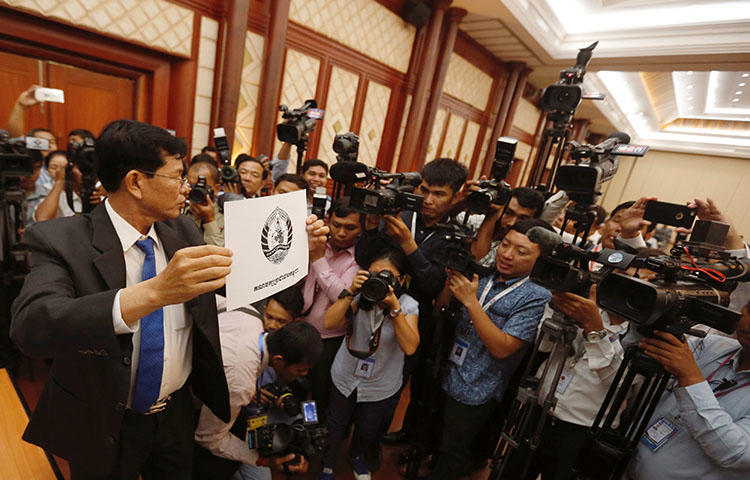A National Election Committee officer in Phnom Penh shows the logo of the ruling Cambodian People's Party during a bid to determine the order of political parties on ballot papers ahead of the country's July election. Cambodia is cracking down on the press ahead of the elections, according to reports. (Reuters/Samrang Pring)