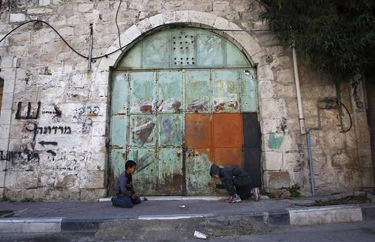 Children play outside a closed store in Hebron in March 2018. Israeli forces arrested a Palestinian photojournalist in the city on June 11. (AFP/Hazem Bader)