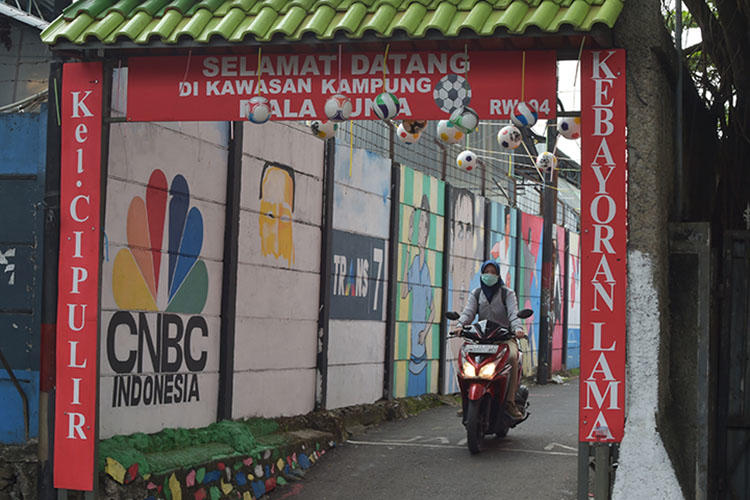 A motorcyclist rides down an alley in Jakarta in June. An Indonesian journalist died while in custody in South Kalimantan. (AFP/Adek Berry)