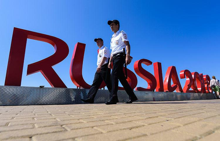 Security personnel walk near the Fisht Olympic Stadium in Sochi on June 12, 2018, two days ahead of the Russia 2018 World Cup football tournament. An imprisoned Russian editor was wounded and hospitalized in Sochi on June 18. (AFP/Jewel Samad)