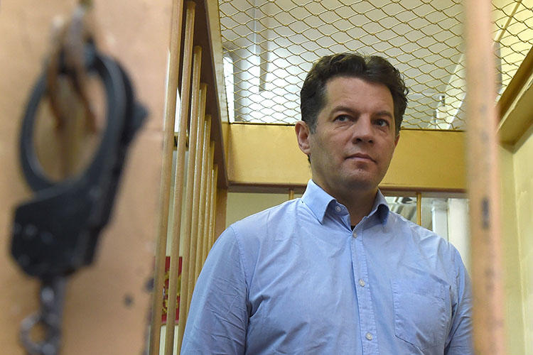 Ukrainian journalist Roman Sushchenko stands inside a defendants' cage during a November 28, 2016, hearing at a court in Moscow. Sushchenko was sentenced to 12 years in prison for espionage by a Moscow city court on June 4, 2018. (Vasily Maximov/AFP)