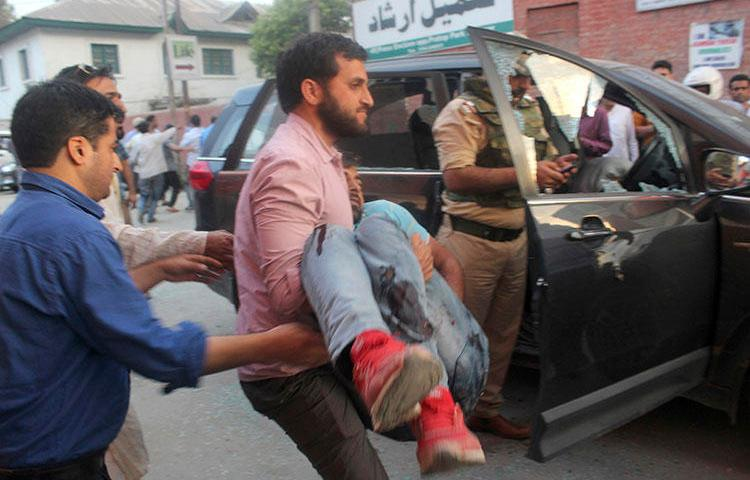 The police bodyguard of journalist Shujaat Bukhari is carried away after an attack in Srinagar, in Indian-controlled Kashmir, on June 14, 2018. Bukhari and two bodyguards were fatally shot as he left his office. (AP Photo)