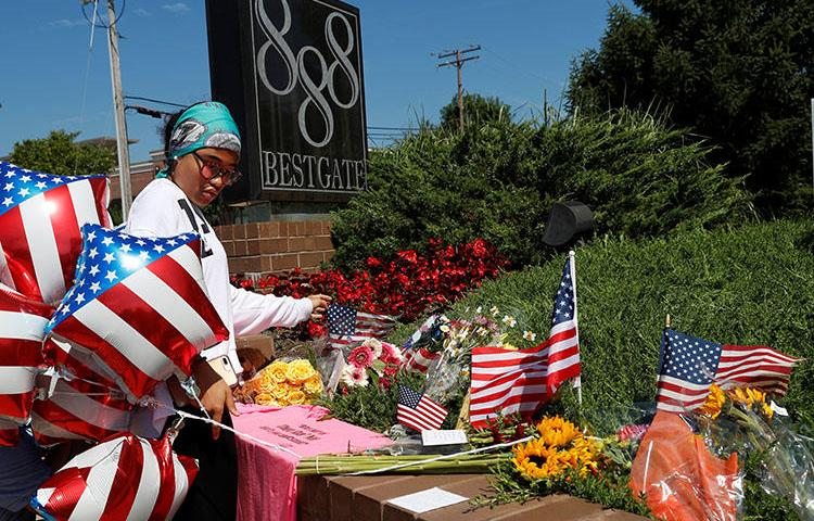 A local resident lays an American flag at an impromptu memorial outside of the Capital Gazette, the day after a gunman killed five people at the newspaper in Annapolis, Maryland, on June 29, 2018. (Reuters/Leah Millis)
