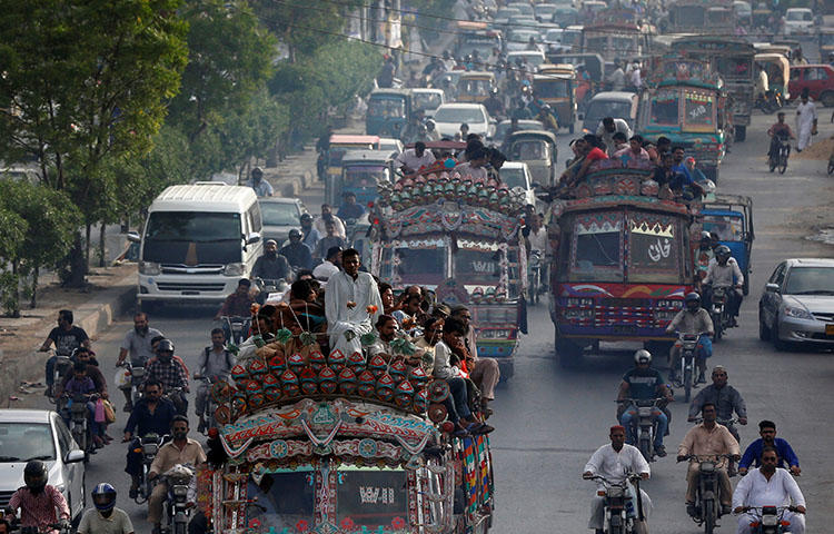 People travel atop vans as they head home during rush hours in Karachi, Pakistan in June 2017. Major General Asif Ghafoor, spokesperson for Pakistan's military and intelligence agencies, accused journalists of sharing anti-state remarks on social media, according to reports. (Reuters/Akhtar Soomro)