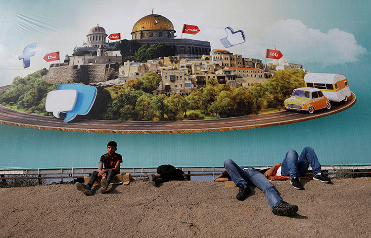 Palestinians rest near an Israeli checkpoint near Ramallah in the West Bank on June 1, 2018. Palestinian authorities to detained Abdul Mohsen Shalaldeh, a reporter for the Hamas-affiliated news website Quds News Network, on June 3, according to reports. (Reuters/Mohamad Torokman)