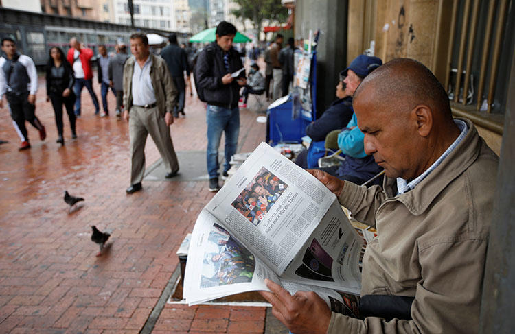 A man reads a newspaper in Bogotá in May. An international court has ordered Colombia to properly pursue justice for a radio journalist killed in 1998. (Reuters/Jaime Saldarriaga)