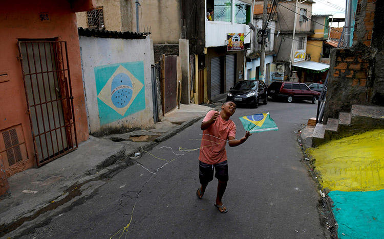 Um menino brinca na rua em Belo Horizonte, Brasil, em 17 de junho. Atacantes mataram um jornalista de rádio no estado do Pará, em 21 de junho. (Reuters/ Washington Alves)