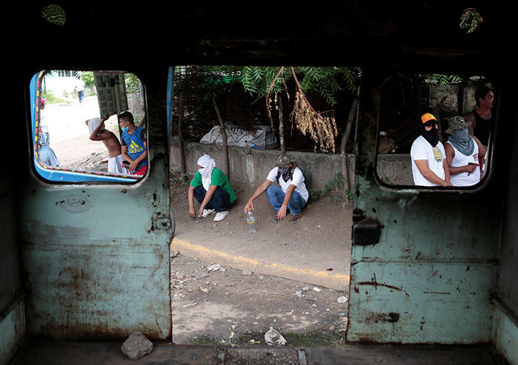 Protesters stand behind a burned bus during an anti-government rally in Tipitapa, Nicaragua on June 14. A Nicaraguan reporter who is covering the unrest says armed attackers broke into his home, beat him, and stole his identification documents. (Reuters/Oswaldo Rivas)