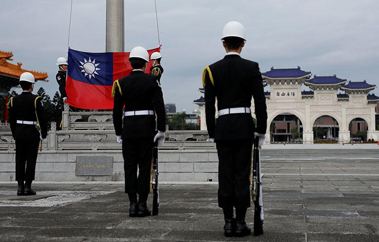 Guards attend a flag-raising ceremony at Taipei's Chiang Kai-shek Memorial Hall in March 2018. Taiwan's parliament is considering a draft bill to penalize 'fake news.' (Reuters/Tyrone Siu)