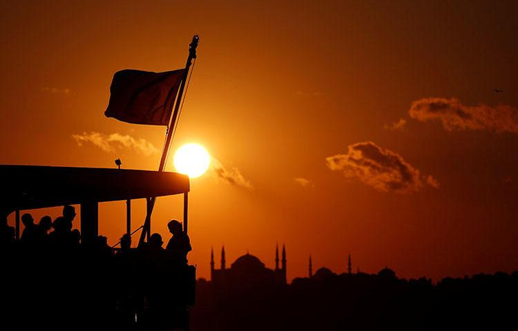 People on a ferry travel across the Bosphorus as the sun sets over the old city in Istanbul, Turkey on July 14, 2018. The Turkish government continues to crackdown on the press over two years after a failed coup attempt, according to reports. (Reuters/Murad Sezer)